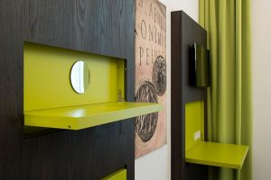 The appealing cabinet finish in a dark coloured, easily maintained wood look is accented with bright spring green sections, which are used as fold-out elements featuring catches made by Häfele.